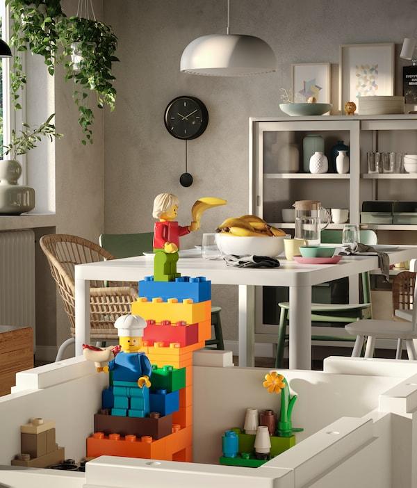 Een witte BYGGLEK doos zonder deksel, en met een kleurrijke set trappen die zijn opgebouwd uit LEGO-stenen die uit de bovenkant van de doos tevoorschijn komen.
