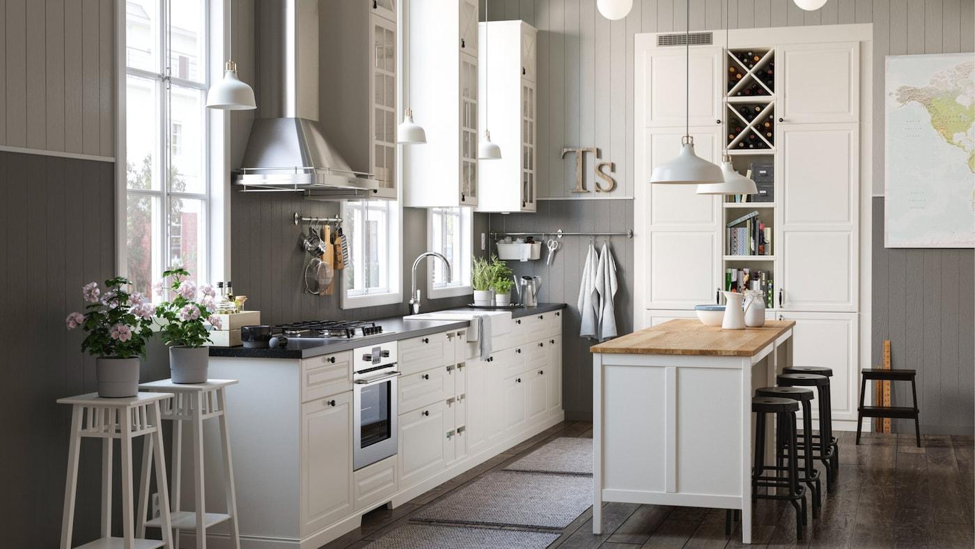Een witte en grijze rustieke keuken met een mix van gesloten en open witte opbergplanken, kasten en een eiland.