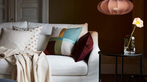 Een witte FÄRLÖV zitbank met verschillende kussens en een plaid naast een zwarte tafel en een REGNSKUR hanglamp.