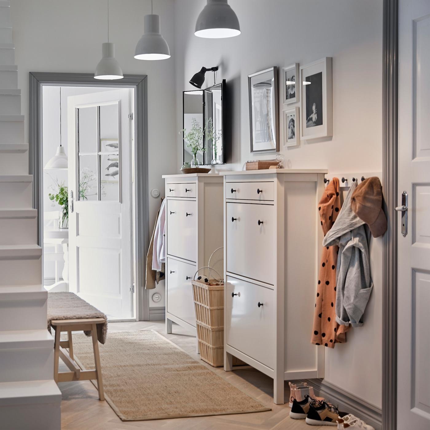 Een witte hal met twee traditionele witte HEMNES schoenenkasten naast elkaar en een kapstok voor de jassen
