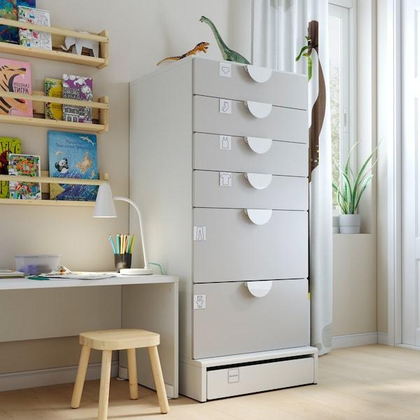 een witte kast met grijze schuiven naast een klein bureautje en een wandrek.