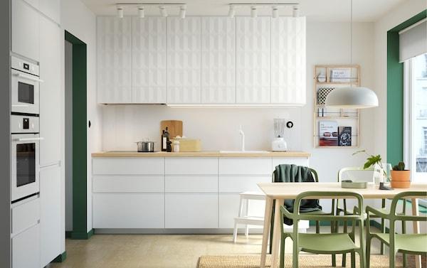 Een witte keuken met groene accenten. De hoogglans witte VOXTORP keukendeuren voor de onderkasten en 3-dimensionele HERRESTAD keukendeuren voor de bovenkasten. Op de voorgrond zie je de LISABO tafel in essenfineer en de YPPERLIG groene stoelen
