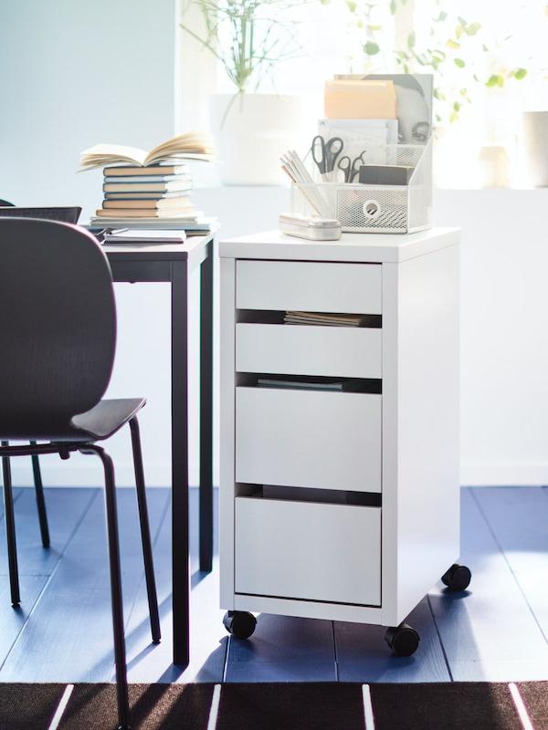 een witte ladeblok staat aan een bureau met stoel