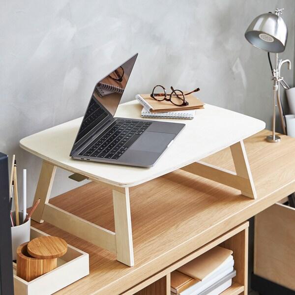 Een witte laptopondersteuning met een laptop en een bril erop, bovenop een licht houten bureau met aan één kant een zilveren bureaulamp.
