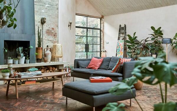 Een woonkamer in de stijl van een pakhuis, met bakstenen muren, open haard, parketvloer, blauwe bank en voetenbank, salontafel en planten.