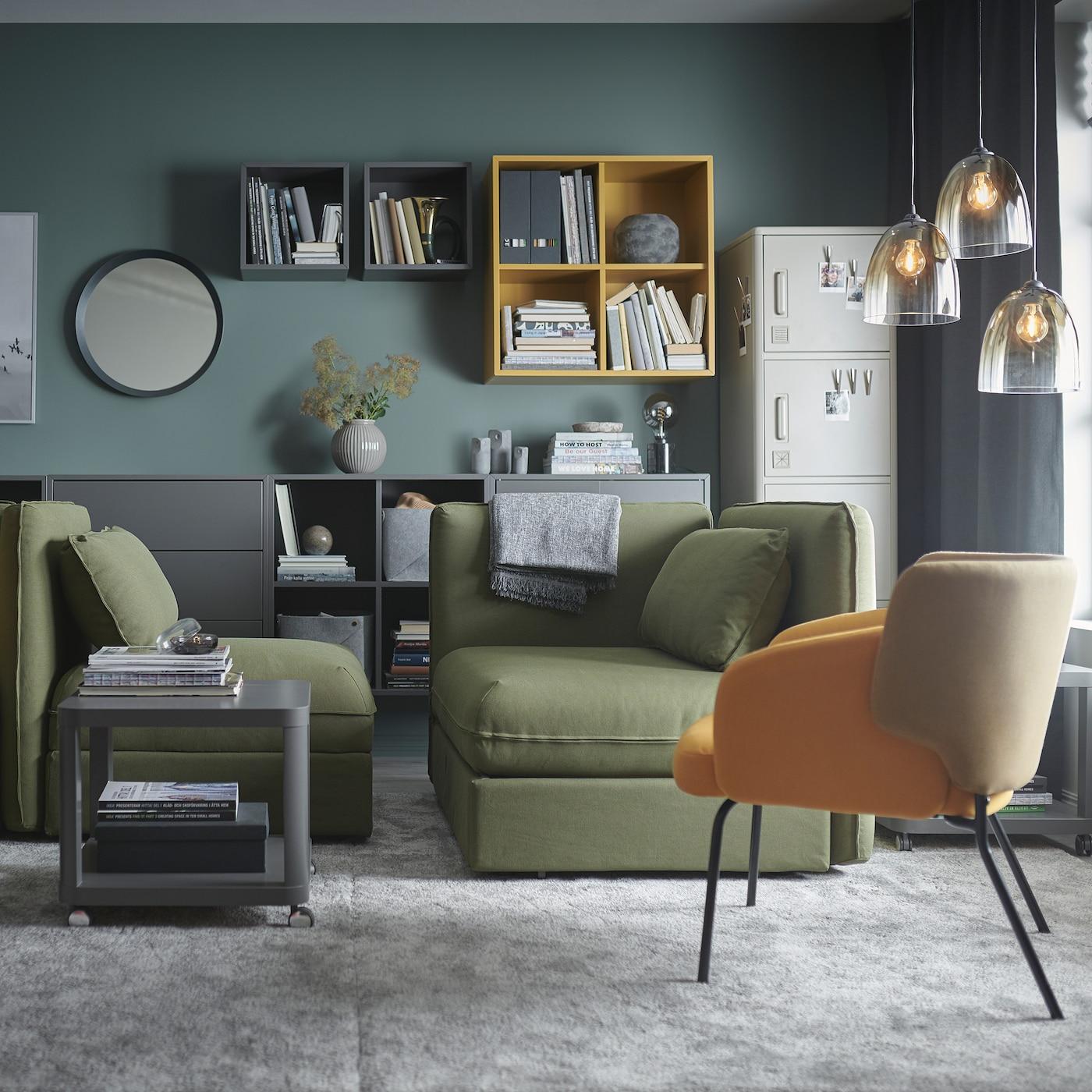 Een woonkamer met groene VALLENTUNA modulaire slaapbanken, grijze grote tapijten, grijze en gele kasten en glazen hanglampen.