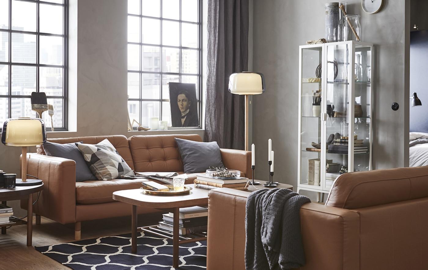Een woonkamer met twee bruine leren zitbanken, een salontafel, een vitrinekast en lampen.