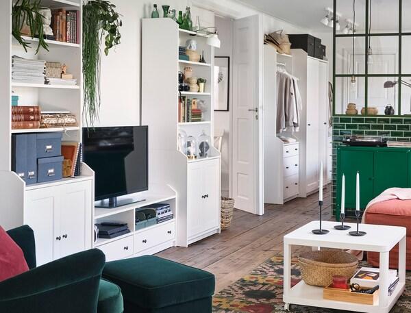 Een woonkamer waar langs een muur een combinatie met HAUGA meubels staan met functionele en decoratieve opbergmogelijkheden.