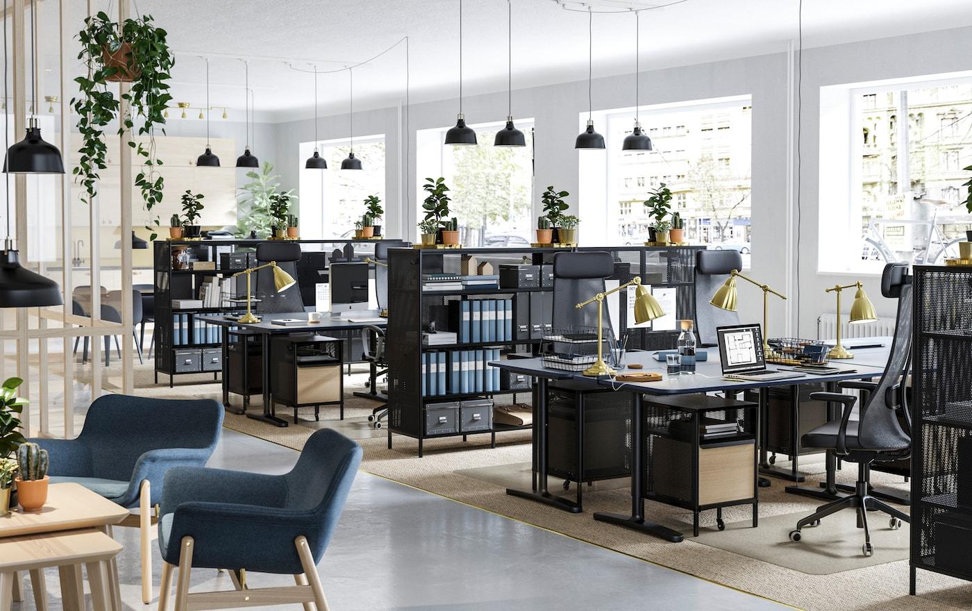 Een zakelijk kantoor met planten op de IKEA BEKANT zwarte opbergrekken en BEKANT zwarte zit-stabureaus.
