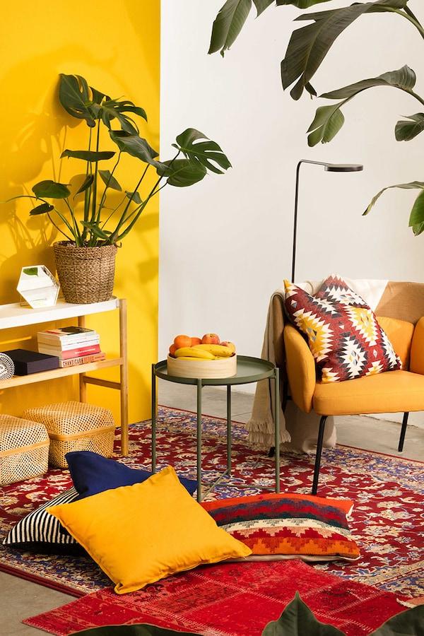 Een zonnig en kleurrijk interieur met planten, gele, oranje en rode accenten en met daarin een gele fauteuil en veel kussens en een Oosters tapijt.