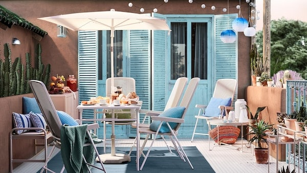 Een zonnig terras met wanden in terracottakleur, blauwe deuren, een witte tafel met parasol, witte tuinstoelen en blauwe kussens.