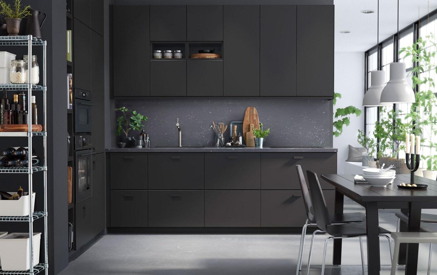 Een zwart grijze keuken en donkergrijze muren en een eettafel.