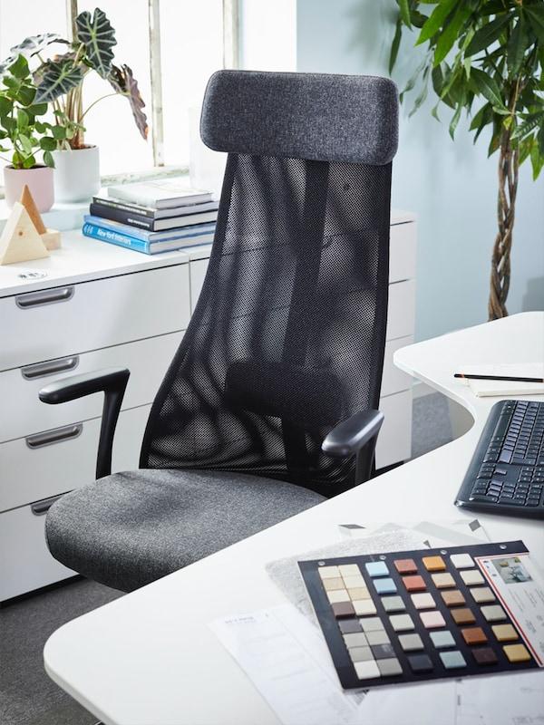 een zwarte bureaustoel met hoge rugleuning aan een bureau