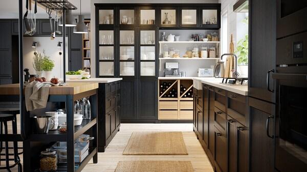 Een zwarte keuken met een houten vloer, wit keukeneiland, zwarte kasten en wijn in een open wijnrek.