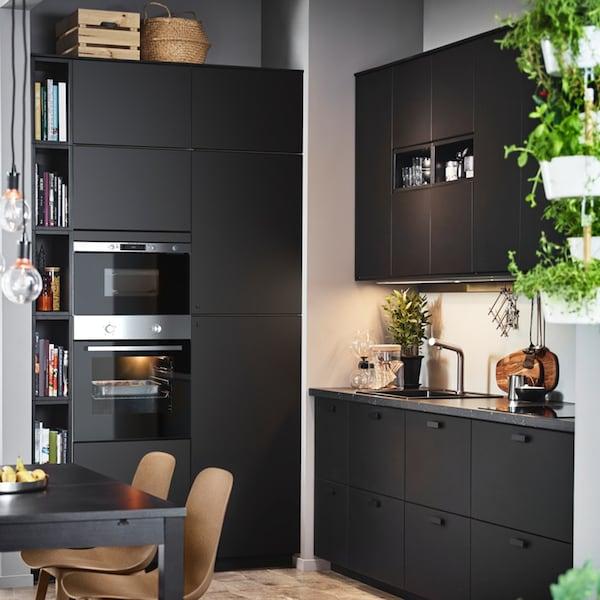 Een zwarte KUNGSBACKA keuken met een oven en magnetron in een hoek.