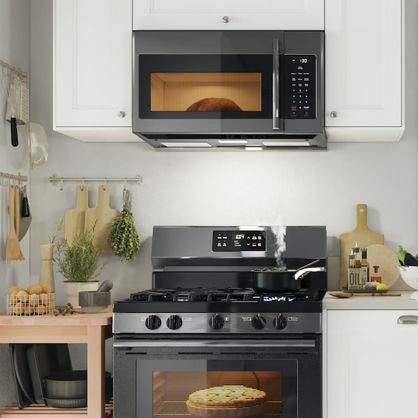 Eggs cooking in a pan on a stovetop, a refrigerator in a clean kitchen, and food cooking in a pan on a cooktop.