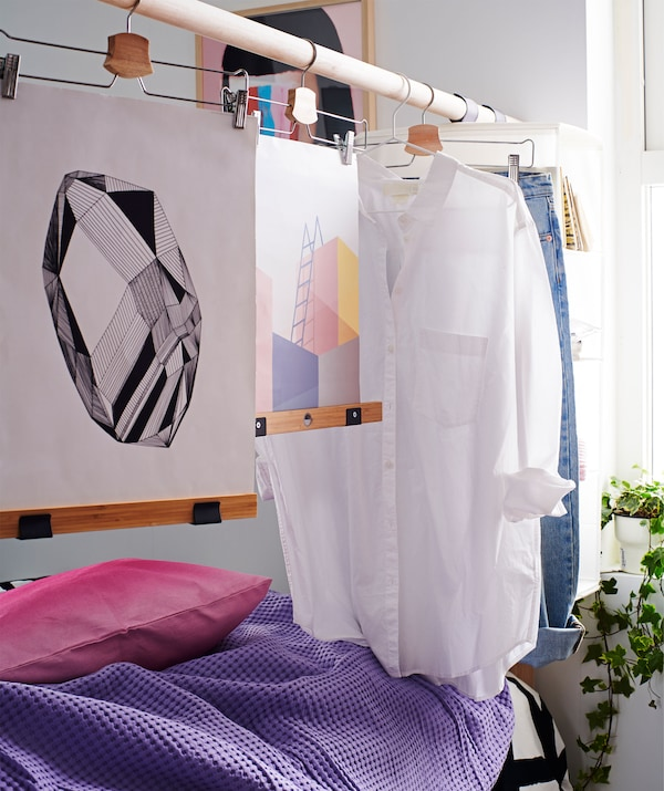 Egy ágy fejtámlája, megemelt rúdból, ruhákkal és alkotásokkal.