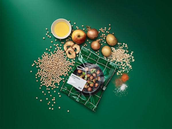 Egy csomag fagyasztott HUVUDROLL húsmentes golyó, körülötte a feldolgozatlan összetevők: zöldborsó, zab, burgonya, hagyma, alma és fűszerek.