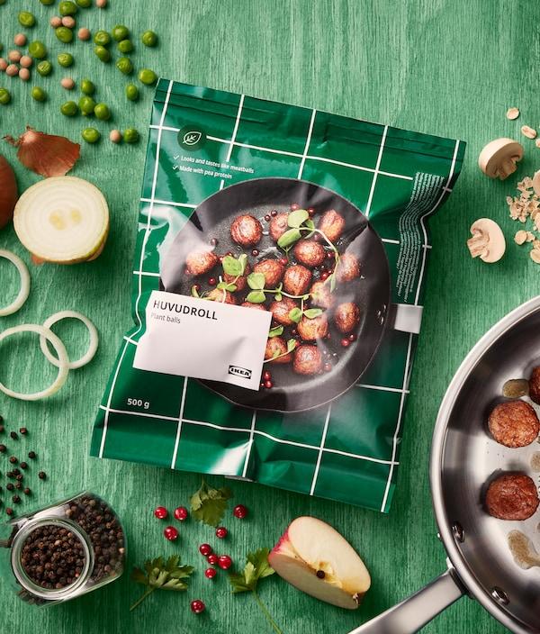 Egy csomag IKEA HUVUDROLL növényi golyó, zöld fa felületre helyezve. A csomagot különféle alapanyagok veszik körül.