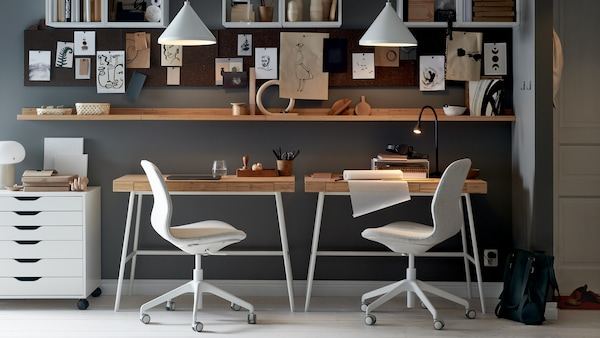 Egy előszobában járunk, ahol a fal előtt álló a két LILLÅSEN íróasztalt irodai székek, egy polcokkal kombinált fehér fiókos elem, üzenőtáblák és fehér függőlámpák egészítik ki.