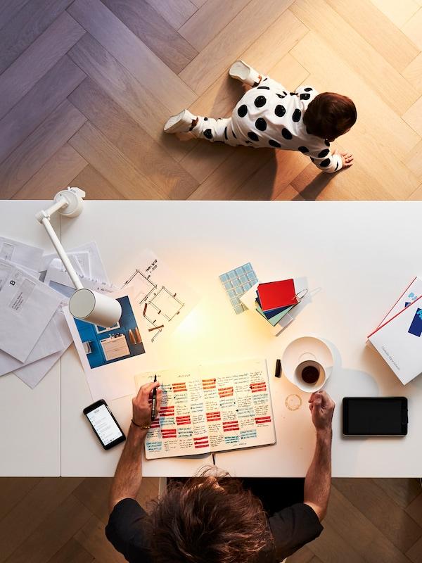 Egy ember az otthoni irodai asztalánál dolgozik egy csésze kávéval, tollal és papírral az asztalon, miközben egy kisbaba mászik a közelében a földön.