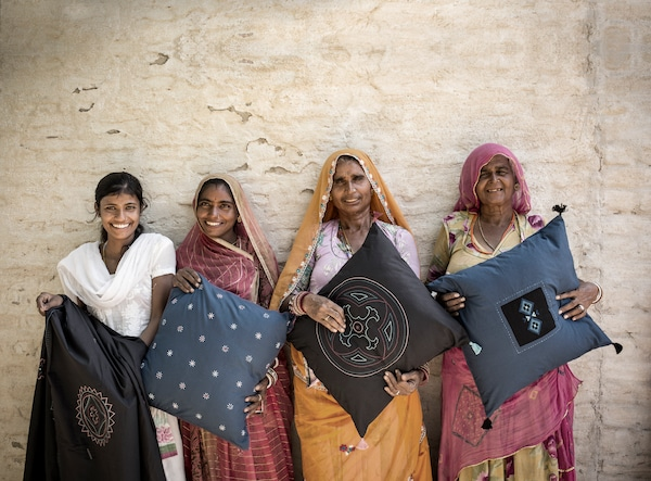 Egy fal előtt négy nő áll kezükben az általuk készített párnákkal.