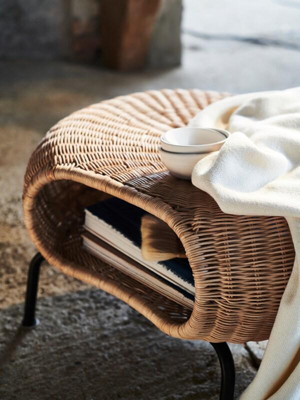 Egy fehér GAMLEHULT lábtartóra vetett fehér takaró, rajta három fehér tál, a lábtartó tárolójában pedig könyvek láthatók.