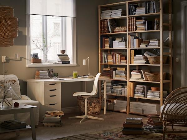 Egy fehér szék és egy íróasztal, könyvespolc a háttérben.