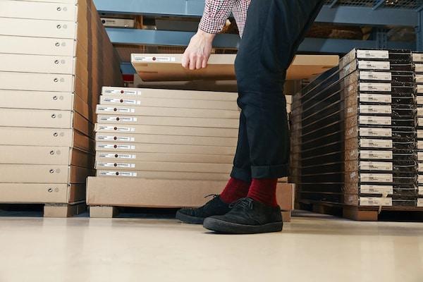 Egy férfi egy becsomagolt terméket emel fel egy IKEA áruházban.