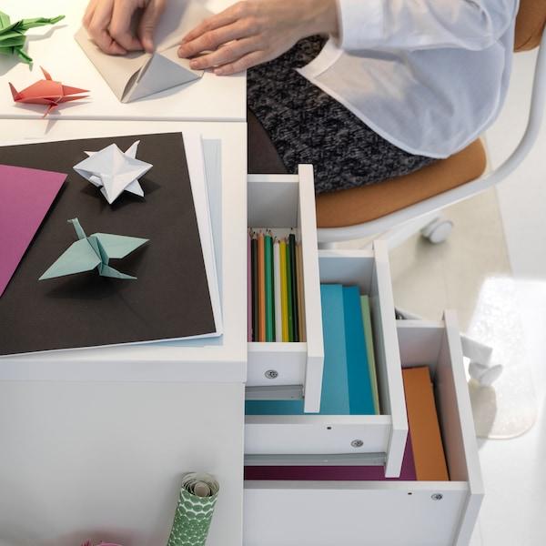 Egy gyerek ül egy fehér asztal és egy fehér MICKE görgős fiókos elem mellett, miközben egy színes papírt mutat.