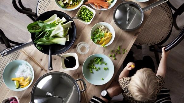 Egy gyermek ül egy felnőtt ölében, ételt eszik egy fából készült asztalnál, tálakban és serpenyőkben gyümölcsök és zöldségek vannak.