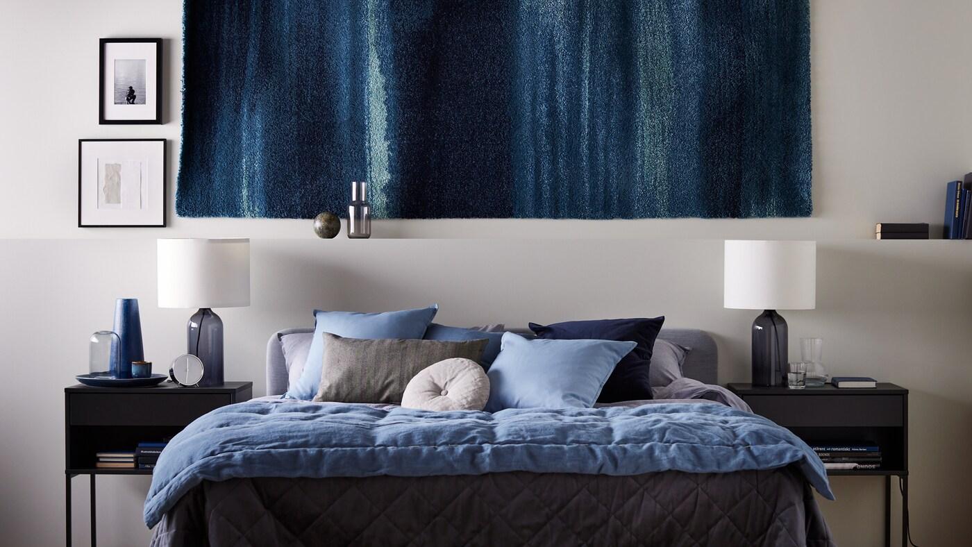 Egy hálószobában járunk, a falon egy faliszőnyeget látunk. Alatta egy világos szürke SLATTUM ágy áll, mindkét oldalán VIKHAMMER éjjeliszekrénnyel. Az ágyon KOPPARBLAD ágynemművel ágyaztak.