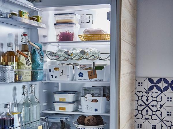 Egy hűtőszekrény belső tere különböző dobozok és üvegek a polcokon.