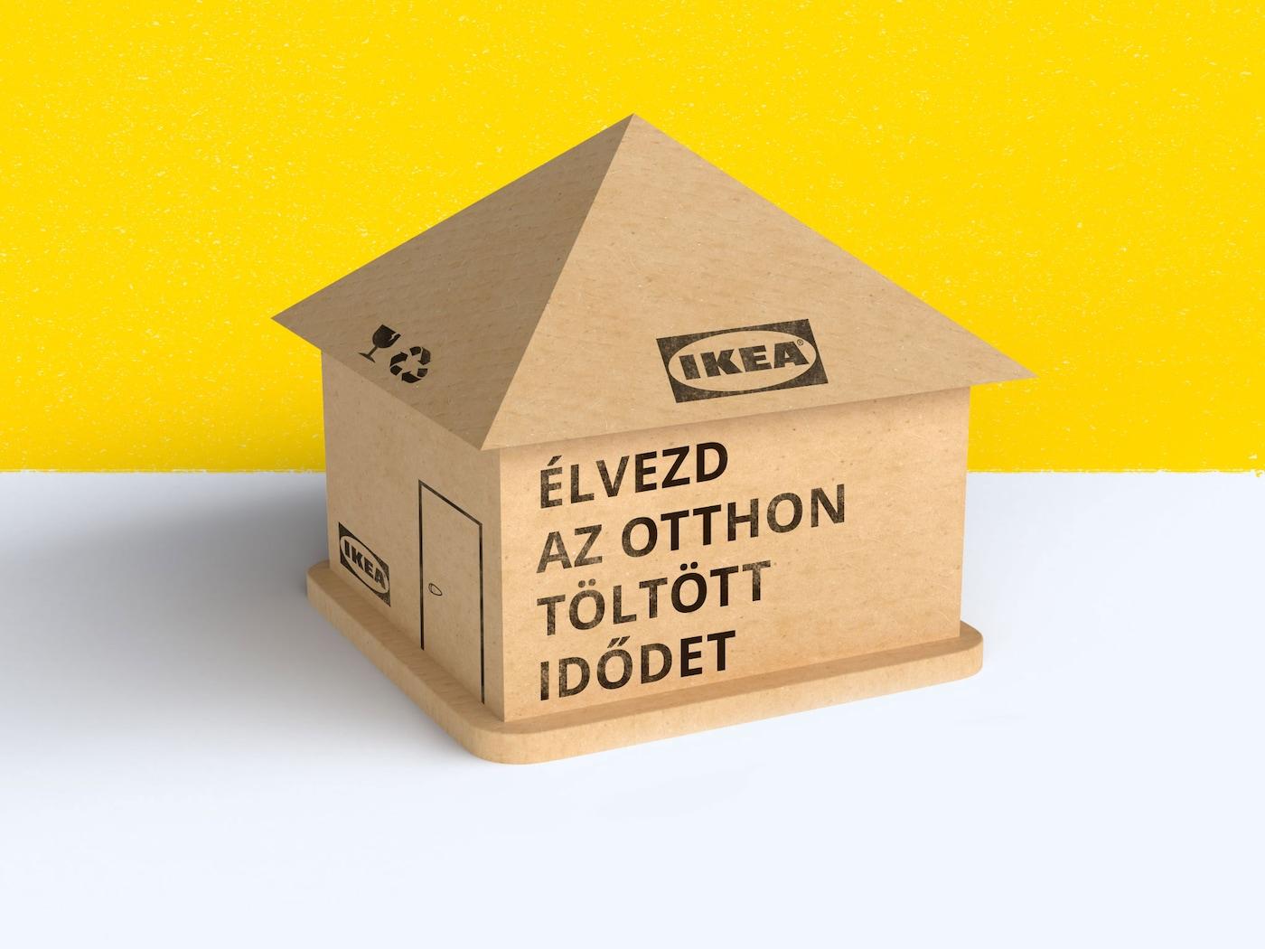 Egy IKEA dobozokból készült házikó, rajta felirat: Élvezd az otthon töltött idődet.