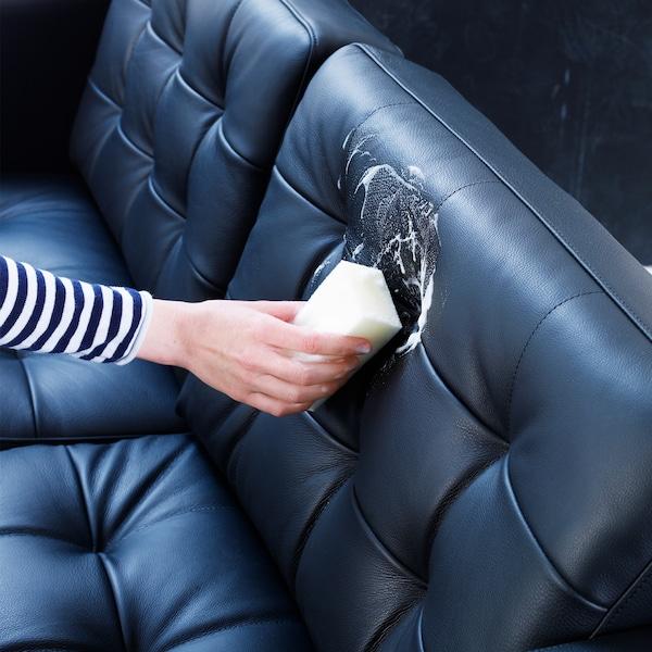 Egy kéz az ABSORB bőrápoló szettből való szivaccsal és folyékony szappannal tisztít egy fekete, kétszemélyes bőrkanapét.