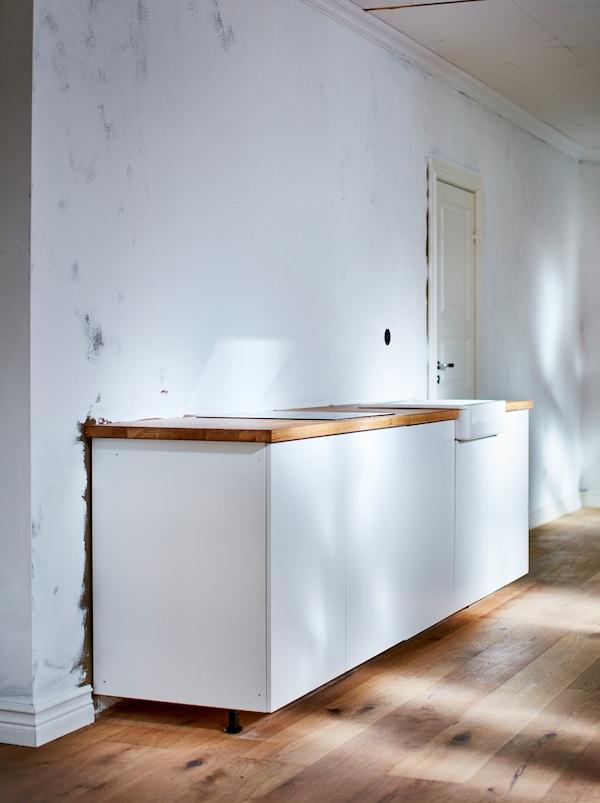 Egy kicsi, fehér, egyszerű konyhabútor fa munkalappal áll a fa padlón egy egyébként üres, fehér falú helyiségben.