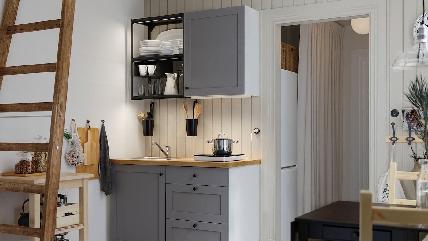 Egy kis konyha antracit szürke színű nyitott polcokkal, fa munkalap, fekete asztal és két fa szék.