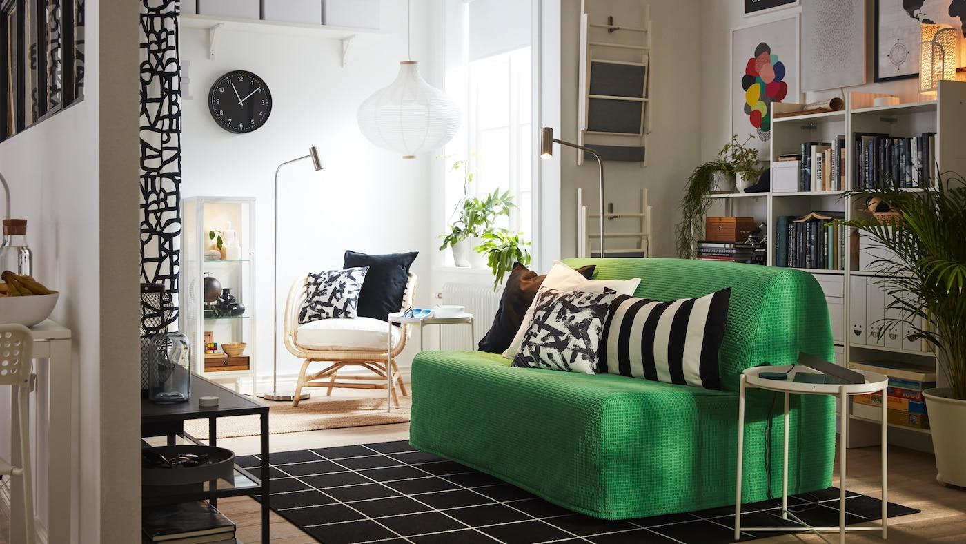 Egy kis stúdiólakás Vansbro élénkzöld színű kétszemélyes kanapéággyal, fekete és fehér textíliákkal, fehér könyvespolccal és karosszékkel.