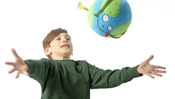 Egy kisfiú feldobja a Földgömb emberkéből készült plüssállatot.