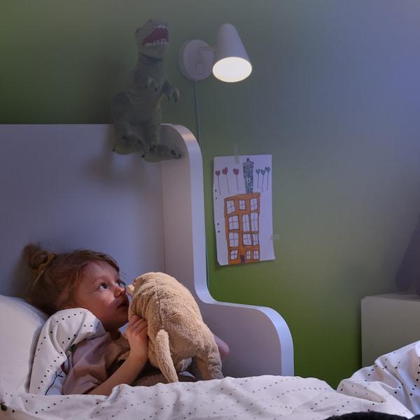Egy kislány fekszik az ágyban, és a kedvenc puha játéka fülébe suttog. A falhoz rögzített FUBBLA fali lámpa kelt lágy fényt a szobájában.