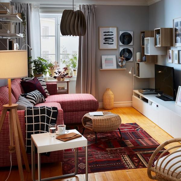 Egy kompakt nappalit látunk egy fekvőfotellel kiegészített kinyitható kanapéval. A szobában tálalószekrény, tároló, tévé, hifi, a falakon pedig keretezett képek is helyete kaptak.
