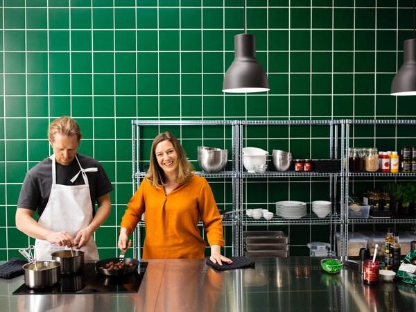 Egy konyhában, melyet a rozsdamentes acél és zöld csempe dominál, egy nő és férfi áll, húsmentes golyókkal teli serpenyővel a kezükben.