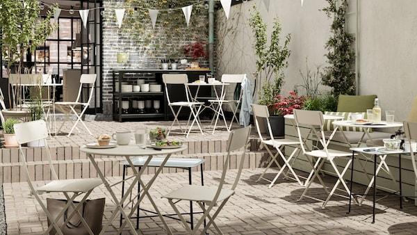 Egy kültéri kávézó bézs színű, fém összecsukható asztalokkal és székekkel, fehér zászlófüzérrel, csempézett padlóval és egy kiszolgálópulttal.