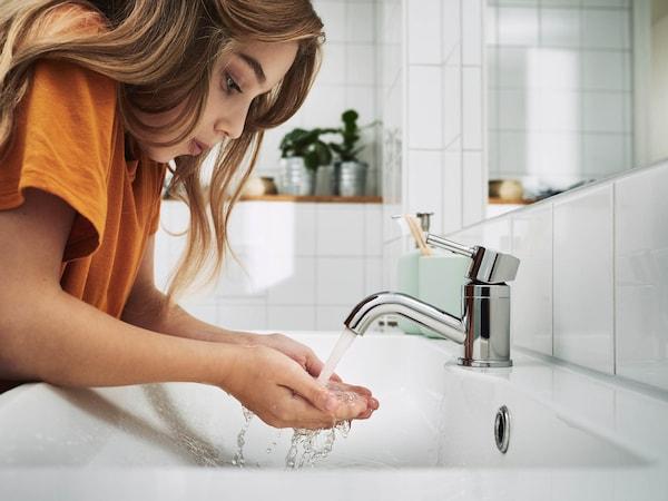 Egy lány egy fehér csempés fürdőszobában vizet folyat a csapból a mosdóba.