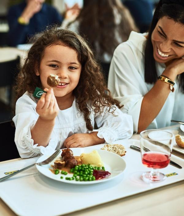 Egy lány egy húsmentes golyót tart mosolyogva. Előtte egy húsmentes golyókkal, pürével és borsóval teli tányér látható.