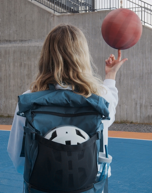 Egy lány kék VÄRLDENS hátizsákot visel, amiben biciklis sisak és vizespalack van, közben az ujján kosárlabdát pörget.
