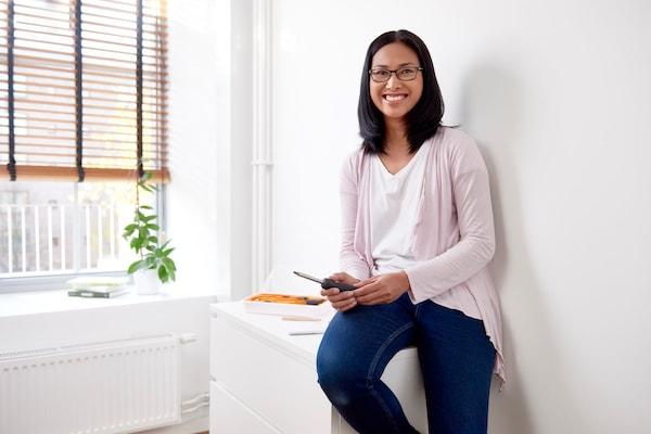 Egy nő egy IKEA komódon ül, csavarhúzóval a kezében.