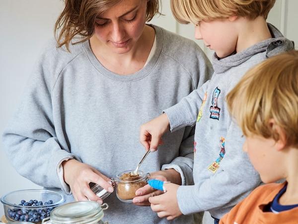 Egy nő két gyermekével reggelit készít csatos üveg edényben, melyben joghurt és granola van.