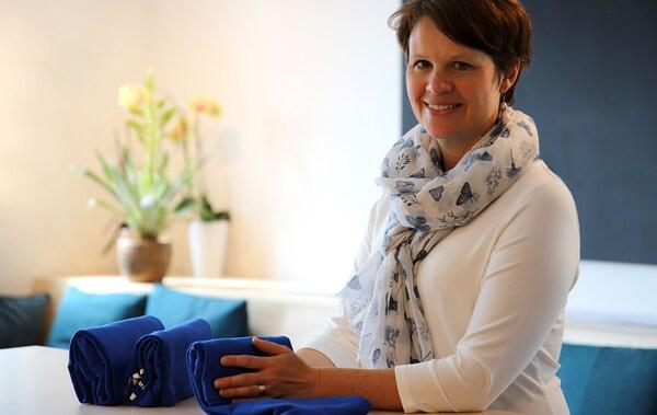 Egy nő ül és mosolyog a kamerába, textileket hajtogat és rak el egy fiókba.