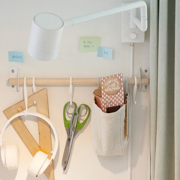 Egy nyír NEREBY sín egy fehér falon, melyről fejhallgató, szögmérő, néhány olló és más, hasonló eszköz lóg.